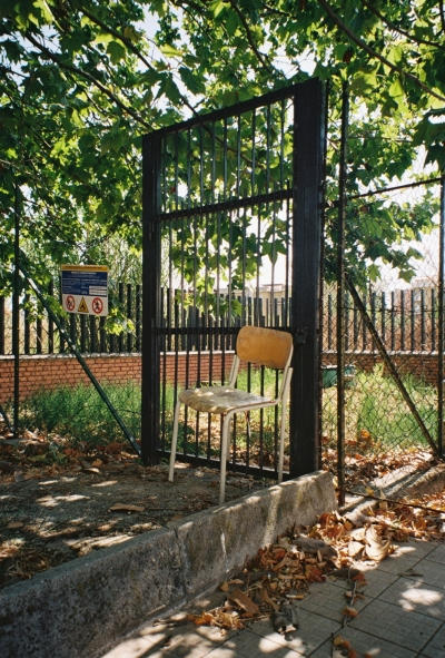 A photo of a chair in front of a fence gate, outdoors