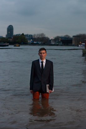 A man wearing the waterproof suit in water and holding a newspaper